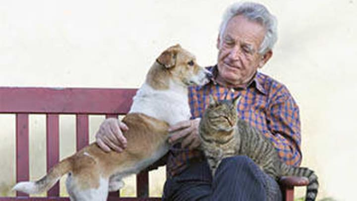 Elderly man sitting with his dog and cat on his lap.