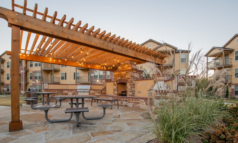 Outdoor barbecue and tables at Portico at Friars Creek Apartments in Temple, Texas