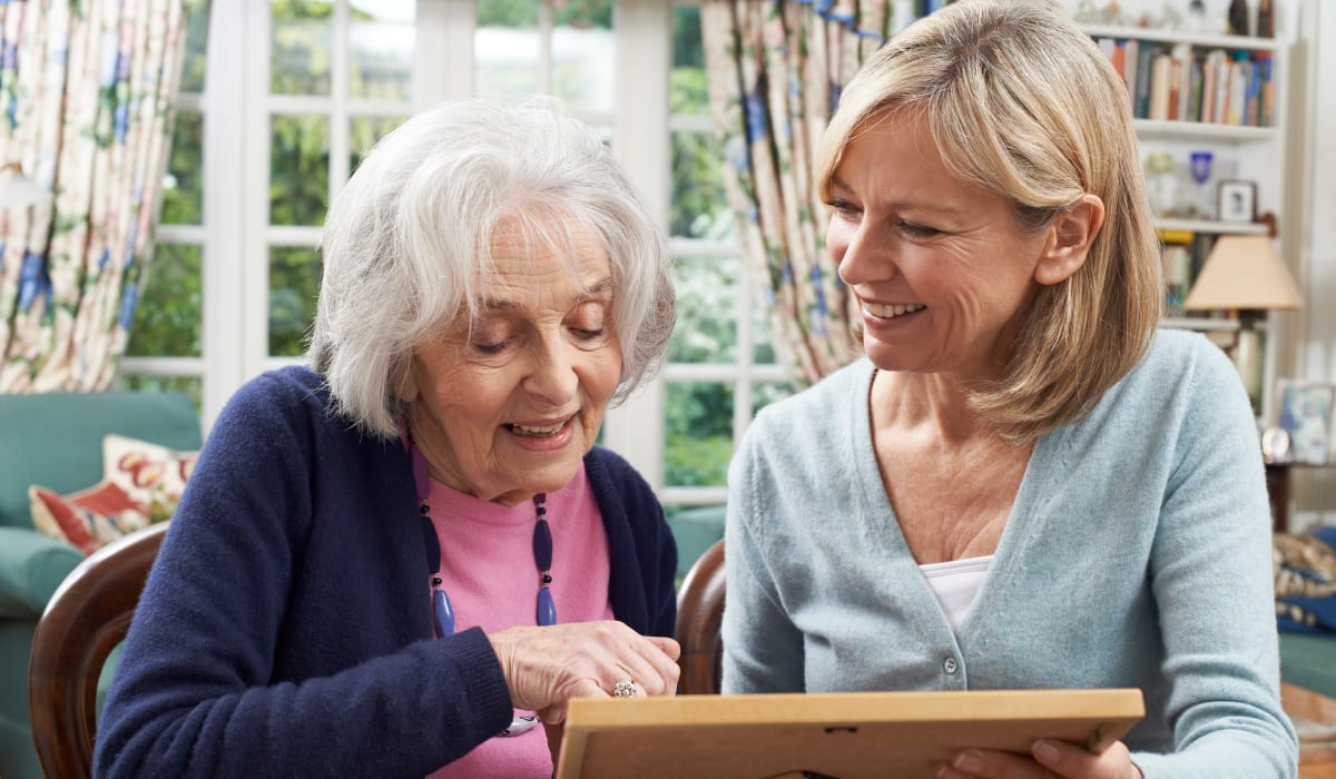 A resident and her daughter looking at a photograph at CERTUS Premier Memory Care Living in Mount Dora, Florida.