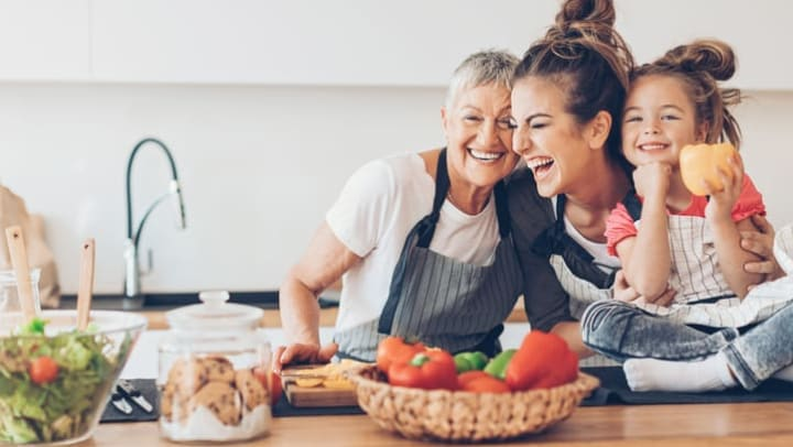 Senior woman, younger woman, and little girl in kitchen embracing each other and laughing near {{location_name}} in {{location_city}}, {{location_state_name}}