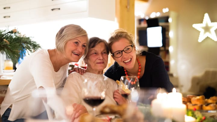Three women hugging at the dining table. Food and glasses of wine are in the foreground.