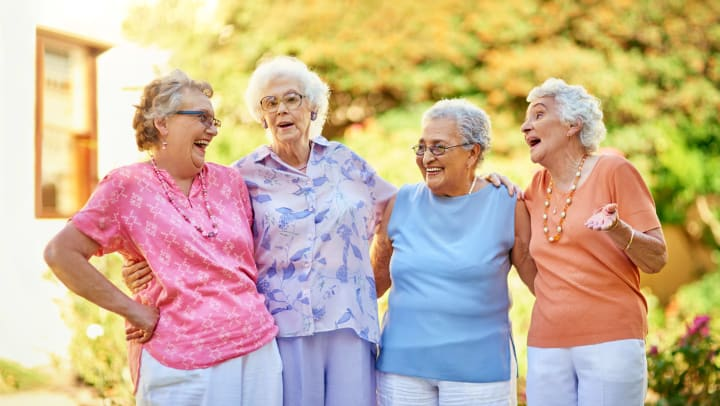 Four elderly women outside standing beside each other smiling.