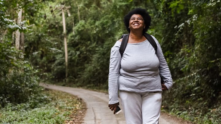 Woman in athletic wear and a backpack standing on an outdoor trail, looking up and smiling.