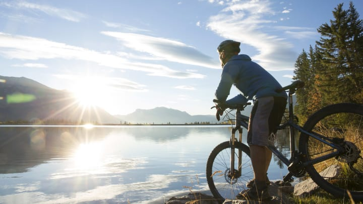 Mountain biker relaxes by lakeshore at sunrise.