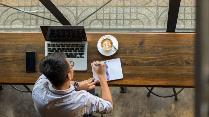 A man studies on his computer and takes notes while drinking coffee in a coffee house