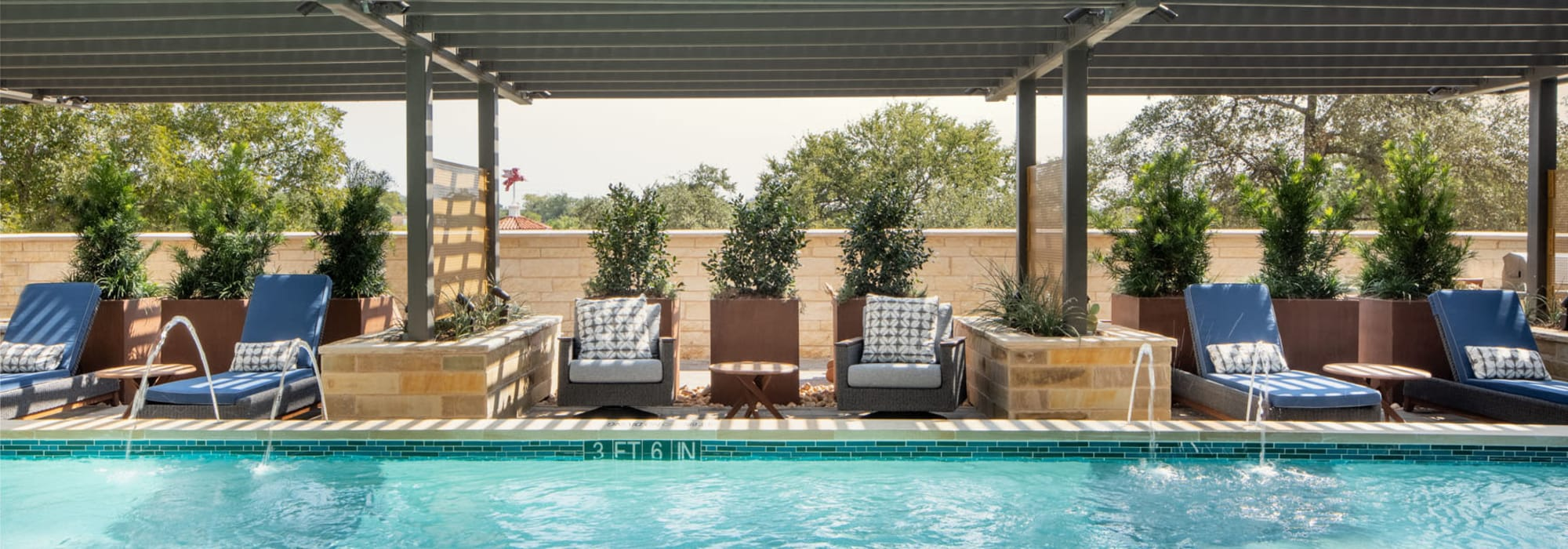 Resort-style swimming pool with shaded lounge seating nearby at Magnolia Heights in San Antonio, Texas