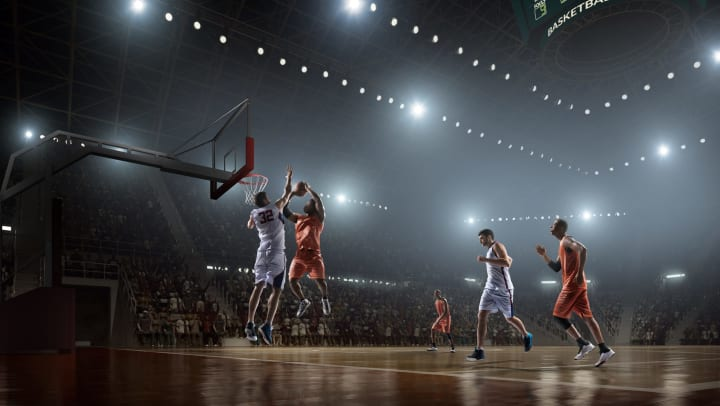 Two basketball teams playing. One player is going for a jump shot while another player from the opposing team attempts to block it.
