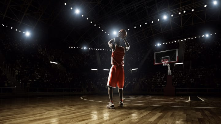 A basketball player on an empty court, shooting a long distance three-pointer.