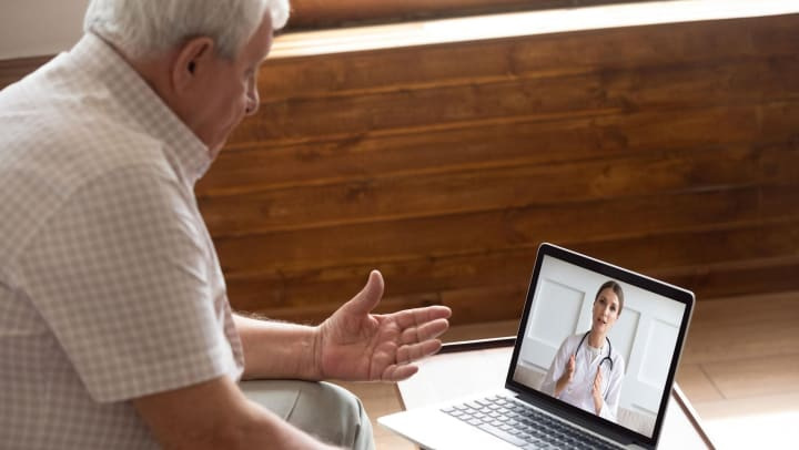 Elderly man communicating with a doctor through a computer