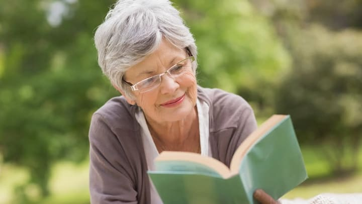 Female senior reading a book outside on a beautiful day.