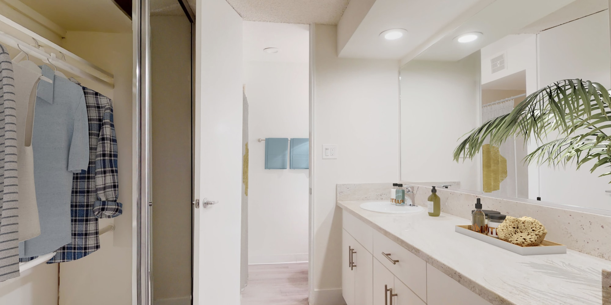 Studio apartment's bathroom with a large vanity mirror and mirrored closet at Mediterranean Village in West Hollywood, California