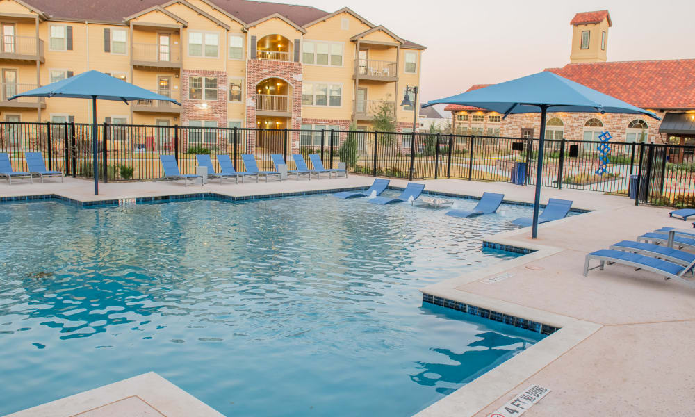 Resort style pool with lounge chairs at Portico at Friars Creek Apartments in Temple, Texas