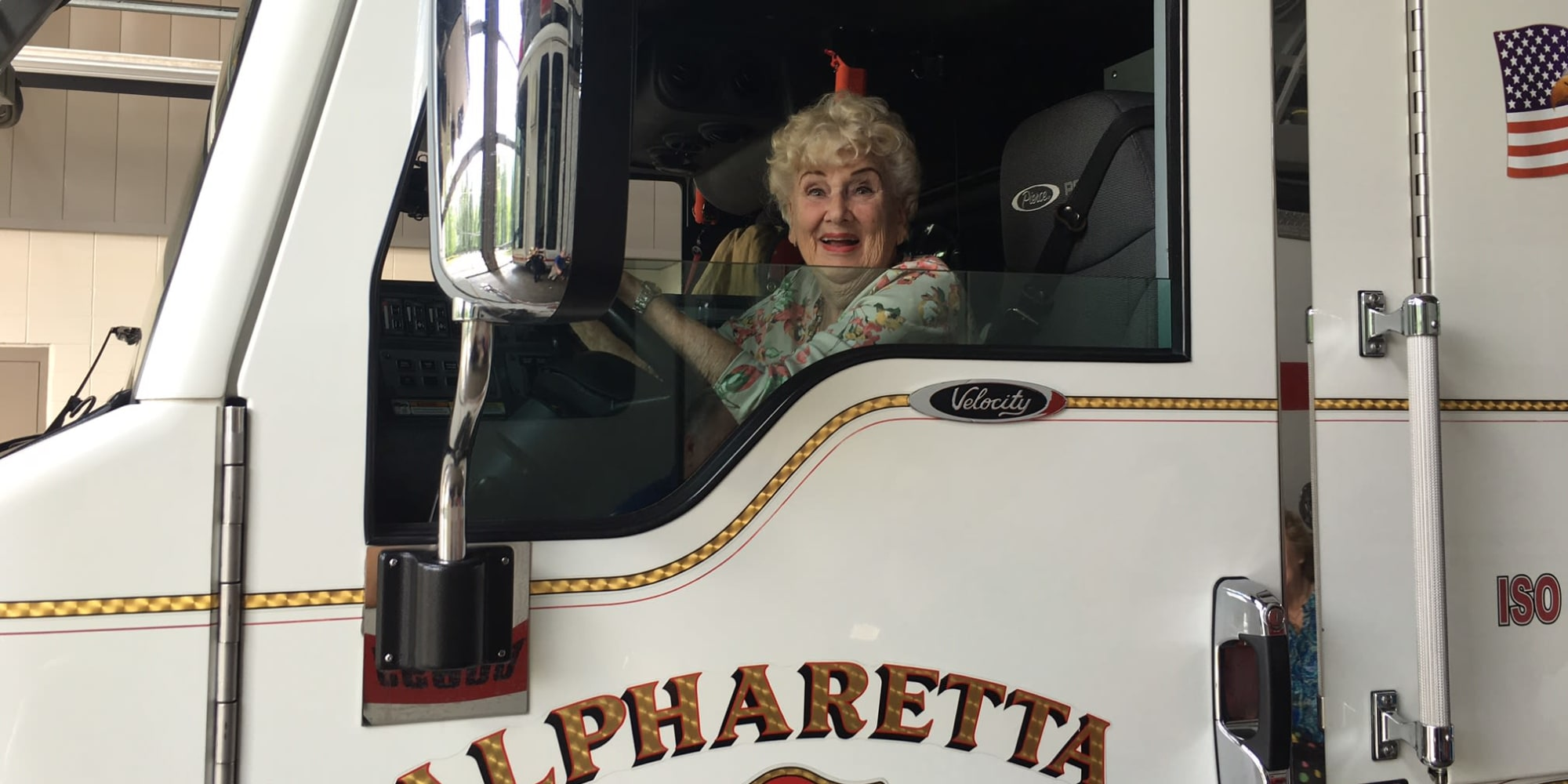 An excited resident from Cottonwood Estates Gracious Retirement Living in Alpharetta, Georgia in the driver's seat of a firetruck