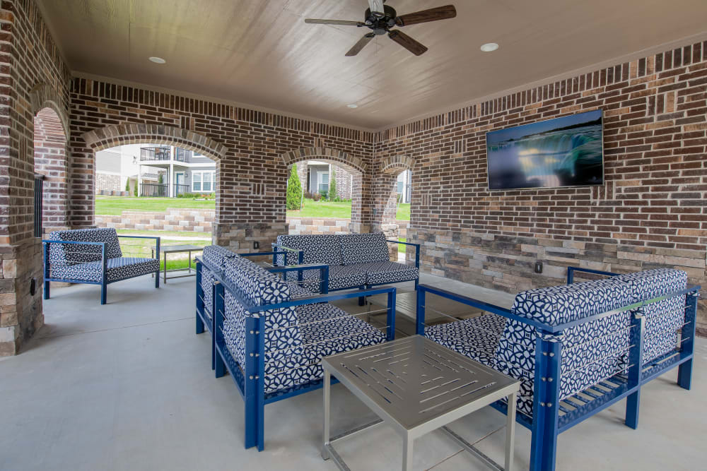 Covered lounge area with television near pool at Cottages at Crestview in Wichita, Kansas