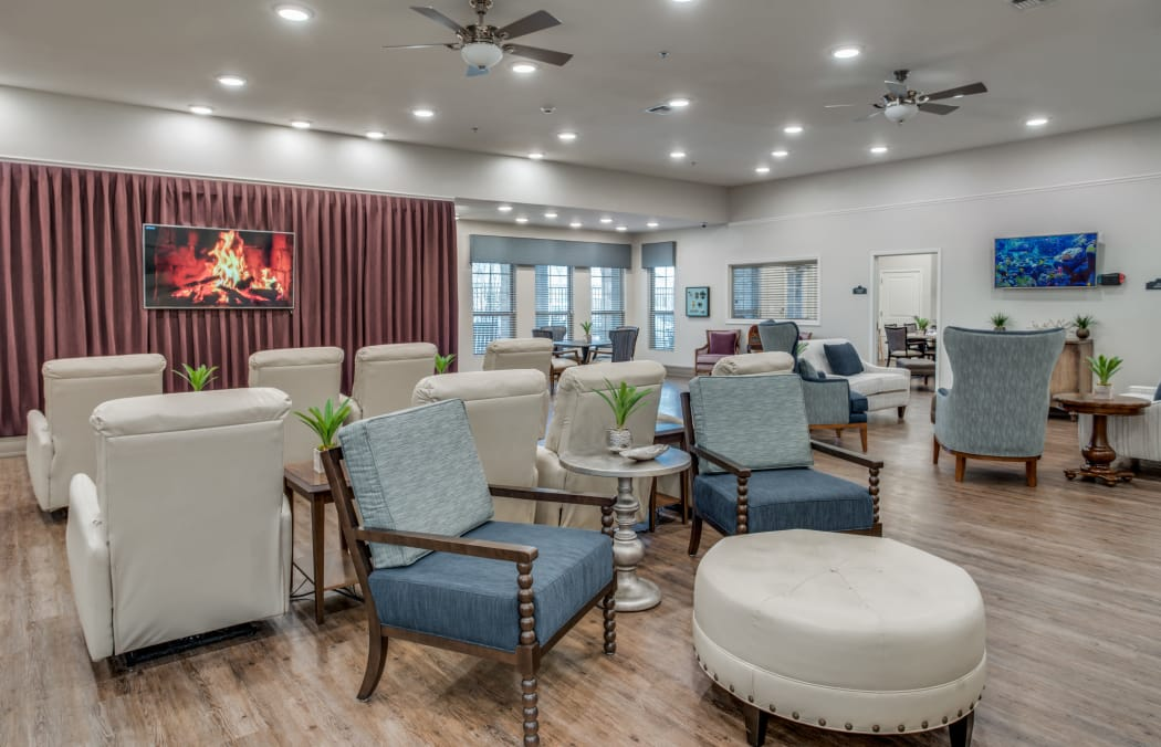 Great Room with comfortable chairs facing a flat-screen television at Iris Memory Care of Turtle Creek in Dallas, Texas.