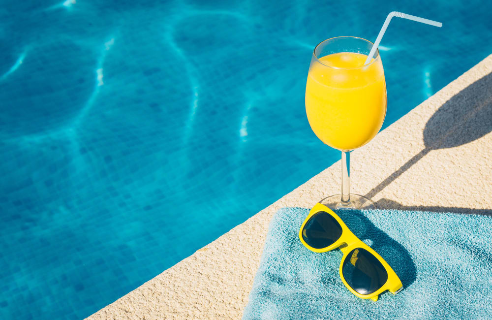 Sunglasses, a drink and a towel by the pool at Orchard Park Apartments in Clarksville, Tennessee