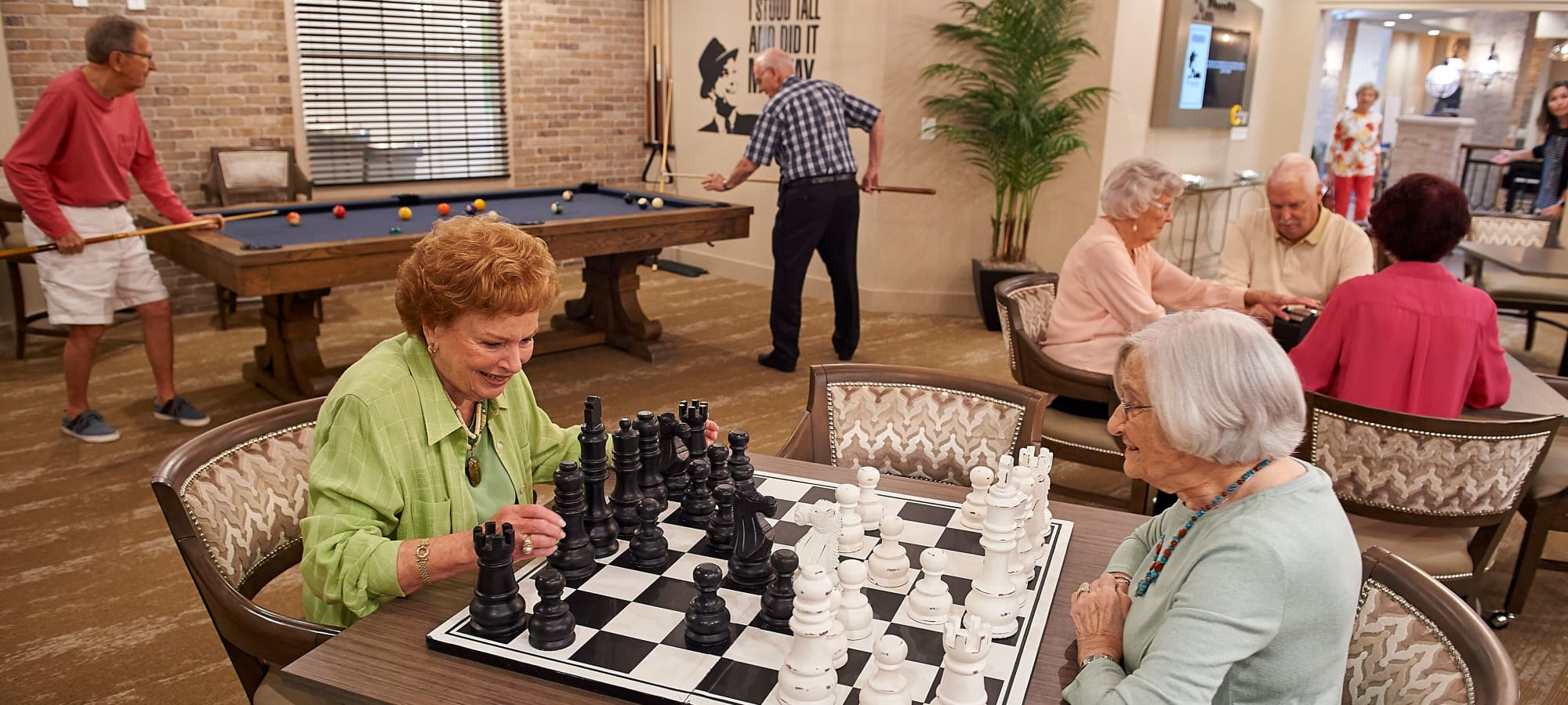Residents playing chess in a game room at AgeWell Living