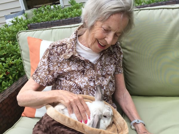 A resident petting a soft bunny at Patriots Glen in Bellevue, Washington.