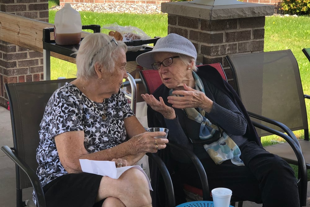 Residents having a conversation on the outdoor patio at Gardenview in Calumet, Michigan