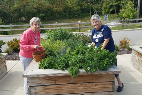 Residents next to a planter box at Magnolia Heights Gracious Retirement Living in Franklin, Massachusetts