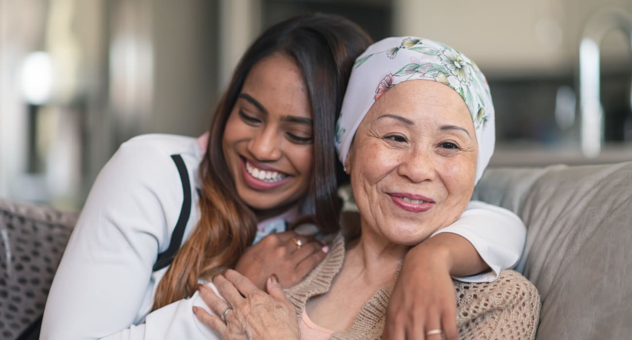A resident and her friend smiling and hugging at Courtyards at Riverpark in Fort Worth, Texas.