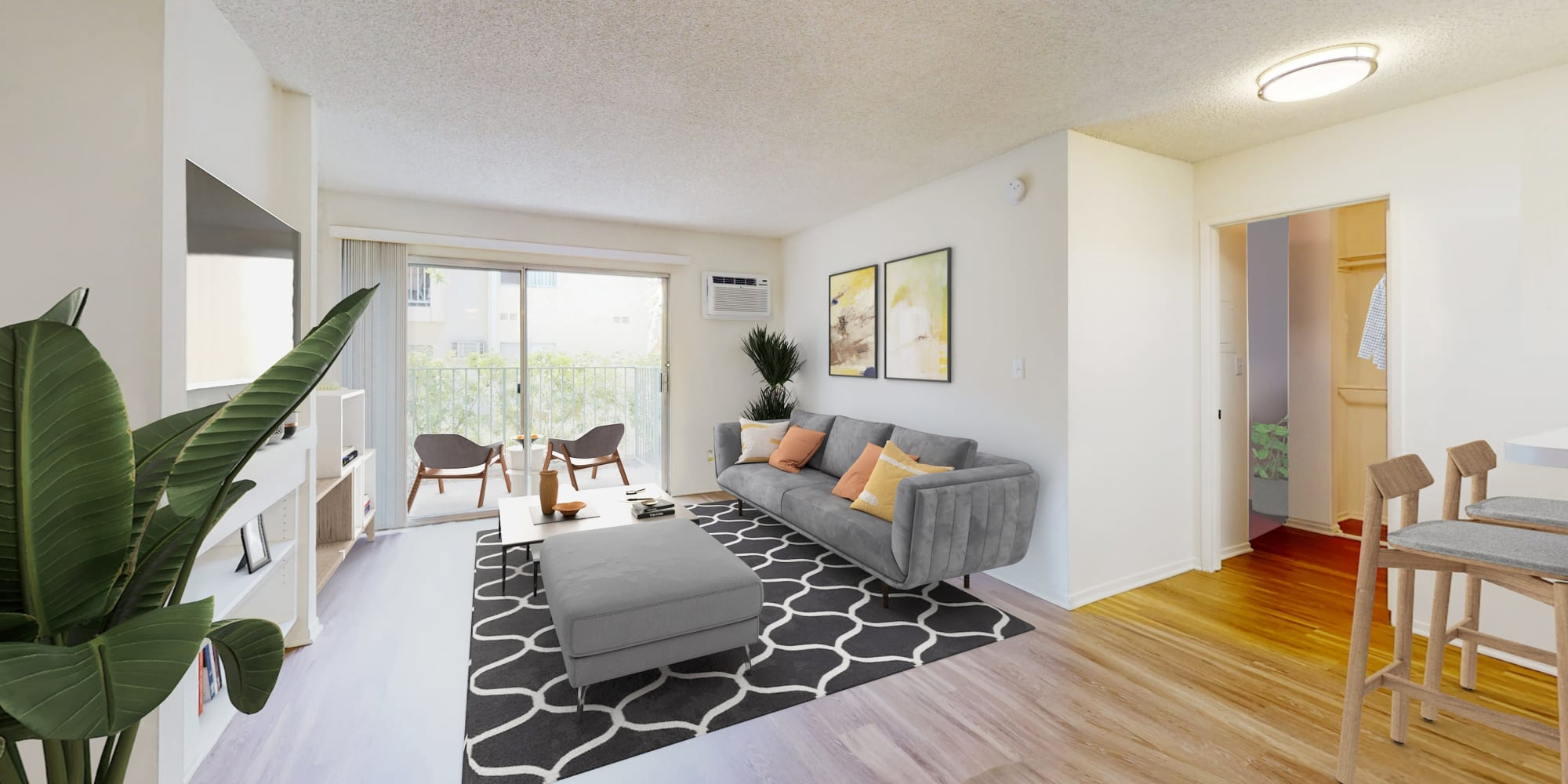 Open-concept living areas with hardwood-style flooring in a model home at Village Pointe in Northridge, California