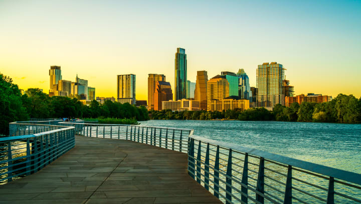 A boardwalk over water with Austin's downtown skyline in the background