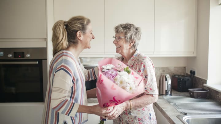 Senior woman smiling and sharing flowers with caregiver