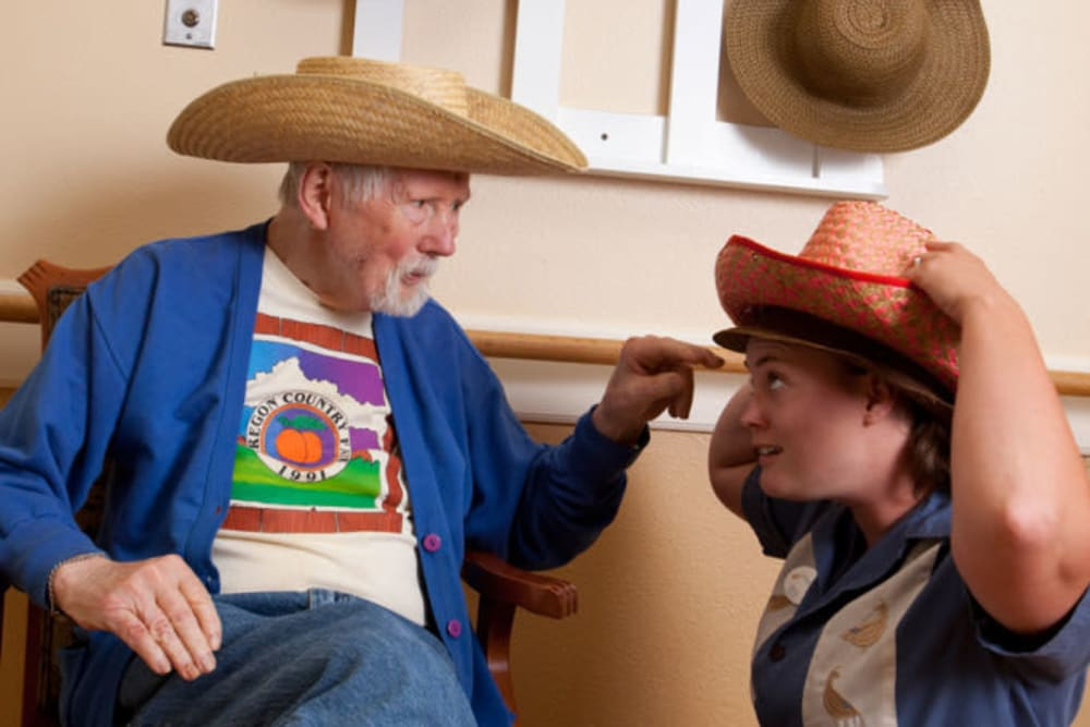 Resident trying on hats with a resident at Quail Park at Morrison Ranch in Gilbert, Arizona