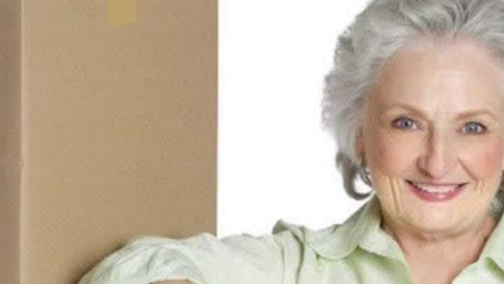 An elderly woman leaning against boxes