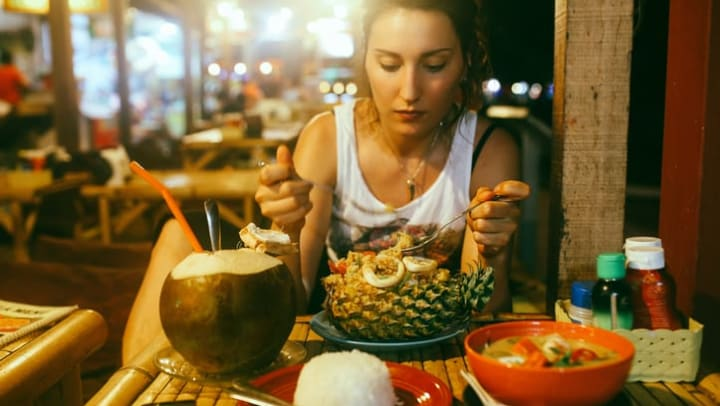Woman eating dinner in a restaurant near {{location_name}} in {{location_city}}, {{location_state_name}}.