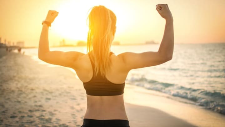 Woman flexes her muscles on the beach near {{location_name}}.