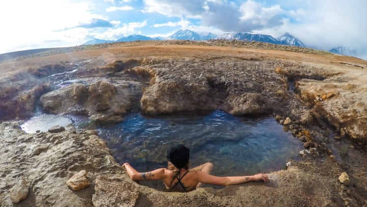 A woman in a bathing suit sitting in a natural hot spring with snow-covered mountains in the distance