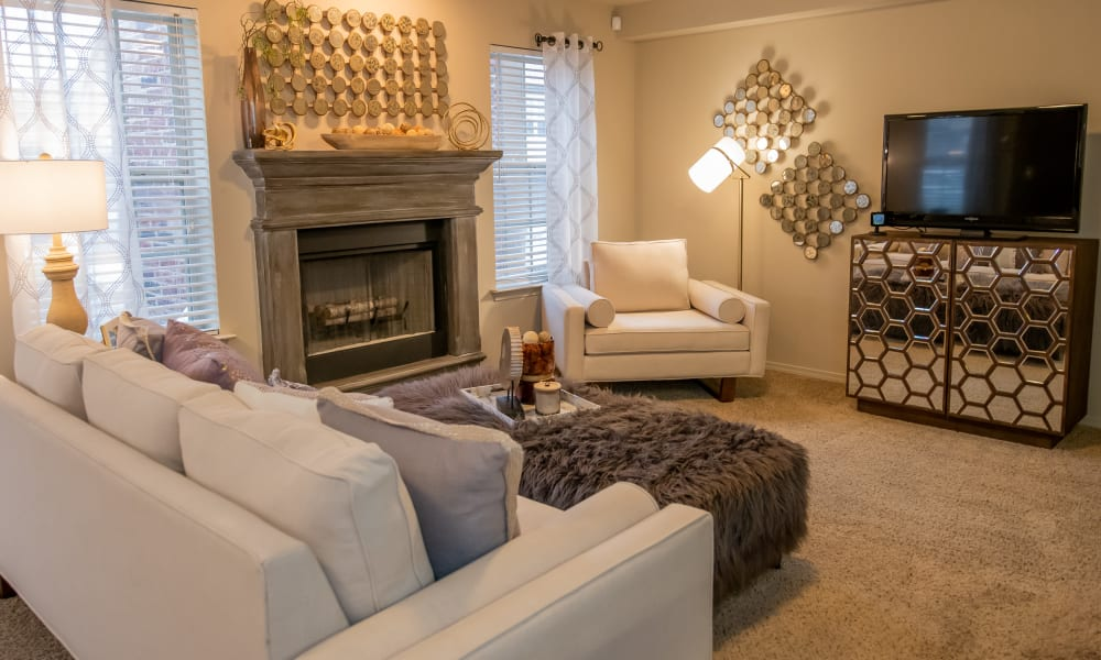 An apartment living room with fireplace at Cascata Apartments in Tulsa, Oklahoma