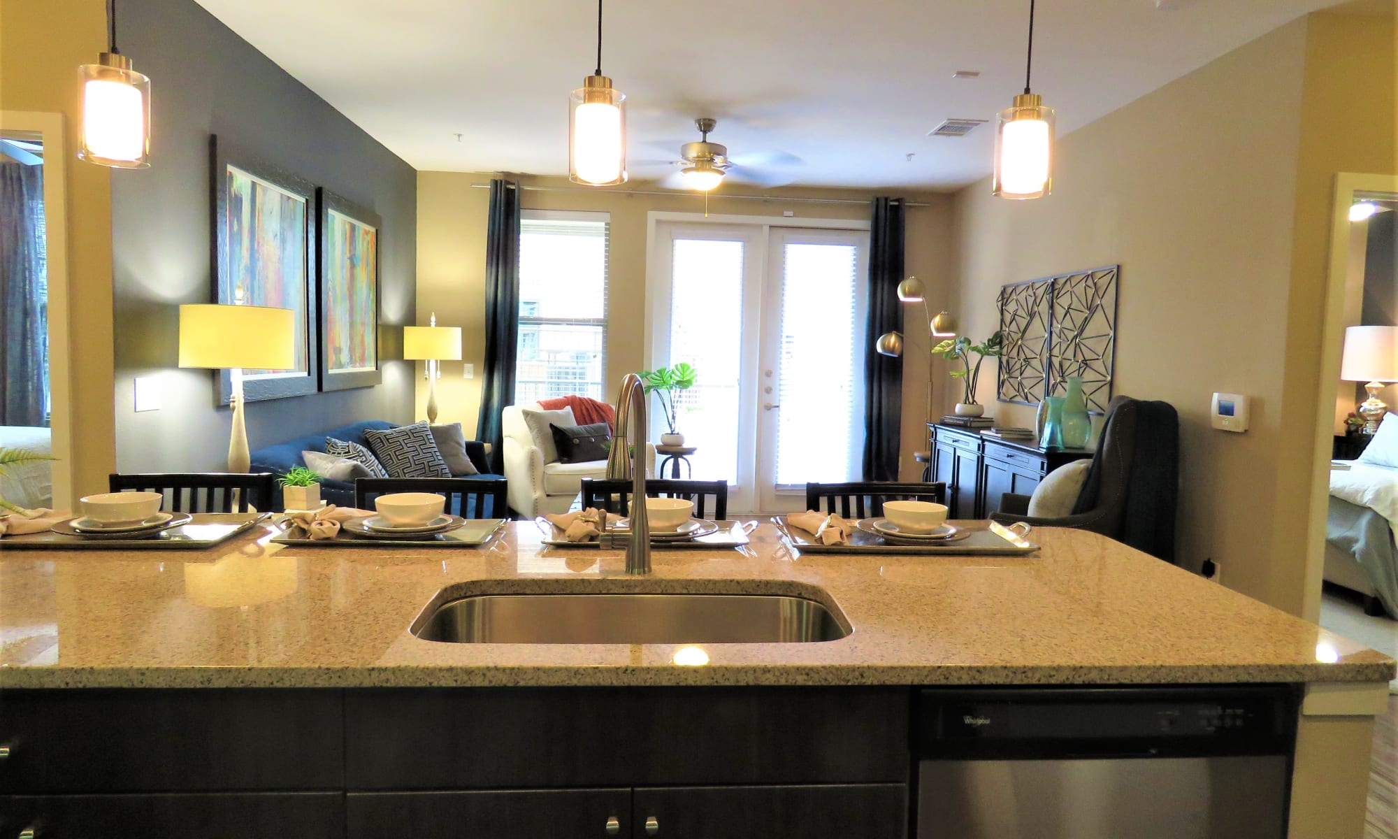 View of living room and kitchen from dining area in model apartment at The Abbey at Spring Town Center in Spring