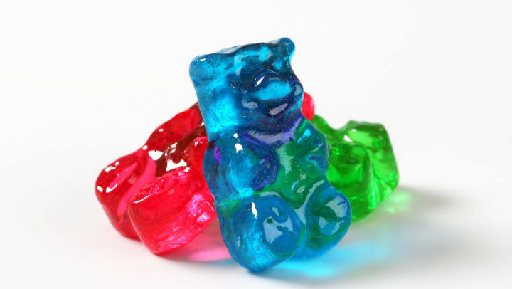Gummy bears leaning against each other, white background.