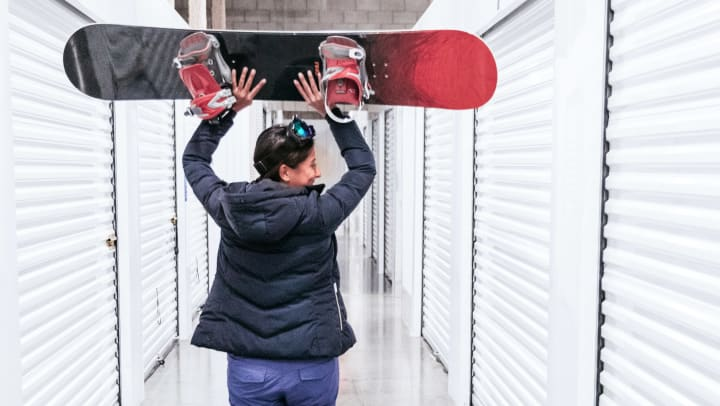 A woman walks through a corridor with storage units while holding a snowboard above her head