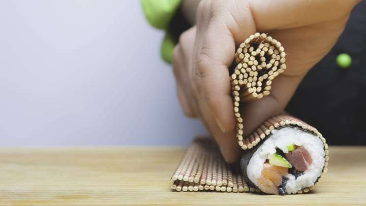 Disembodied hands rolling sushi using a bamboo rolling mat on a wood table.