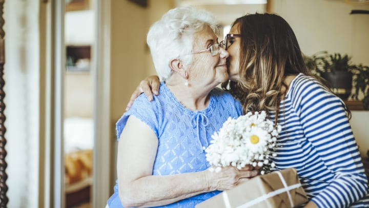 Younger woman kissing older woman on the cheek. Younger woman is holding a wrapped package and older woman is holding flowers.