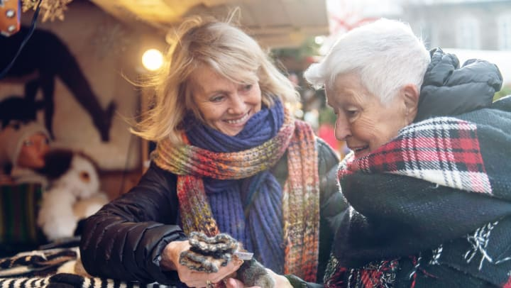 Senior woman and younger woman examining wool gloves at an outdoor bizarre.