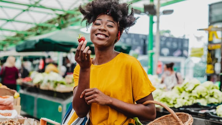 Woman holds up a strawberry at the market