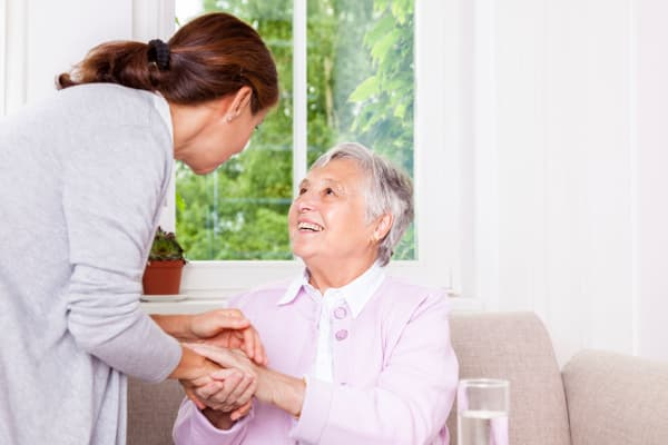 Senior woman laughing with elderly care nurse