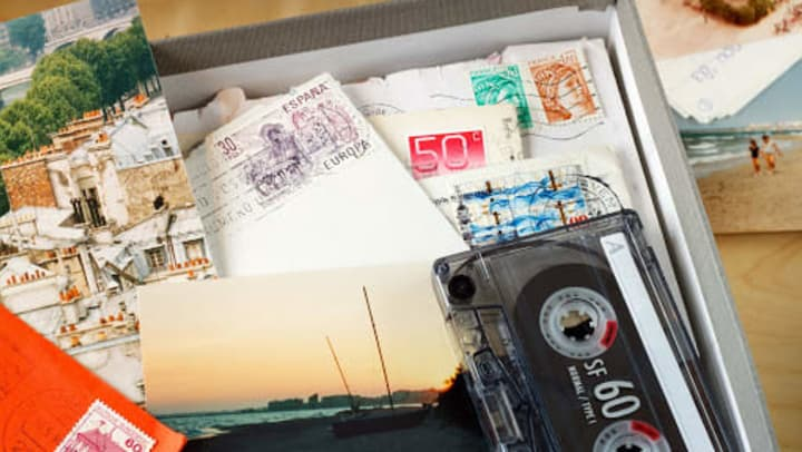 A box filled with letters, photos, and a cassette tape.