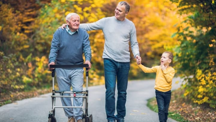 Elderly father, adult son, and grandson out for a walk in the park near {{location_name}}.