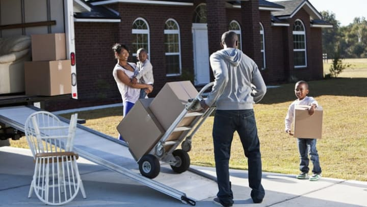 Woman carrying a child watches as man rolls boxes on a dolly into a moving truck. A child holds a box off to the right near {{location_name}} in {{location_city}}, {{location_state_name}}