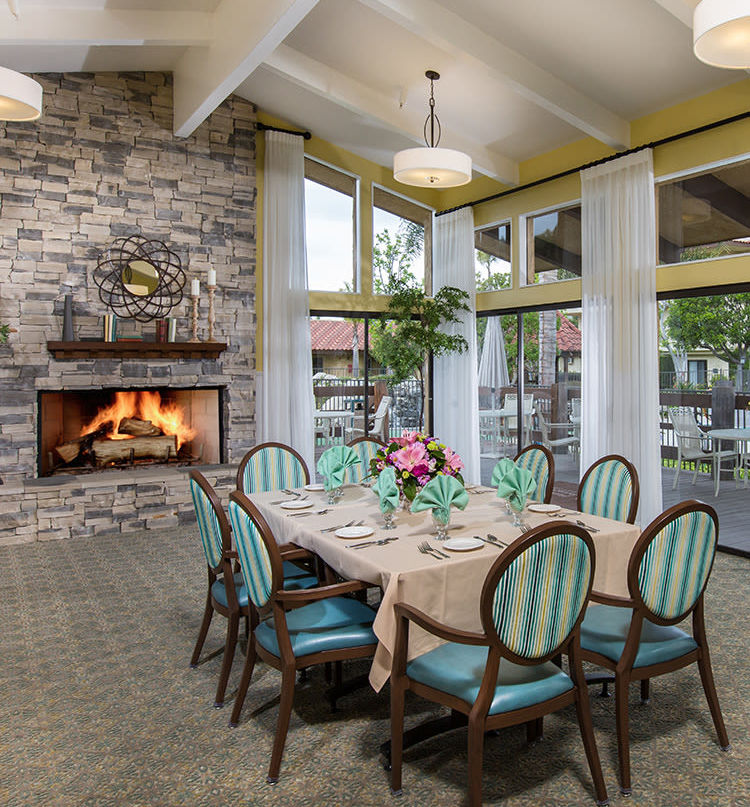 Dining table in front of fire place at Huntington Terrace in Huntington Beach, California