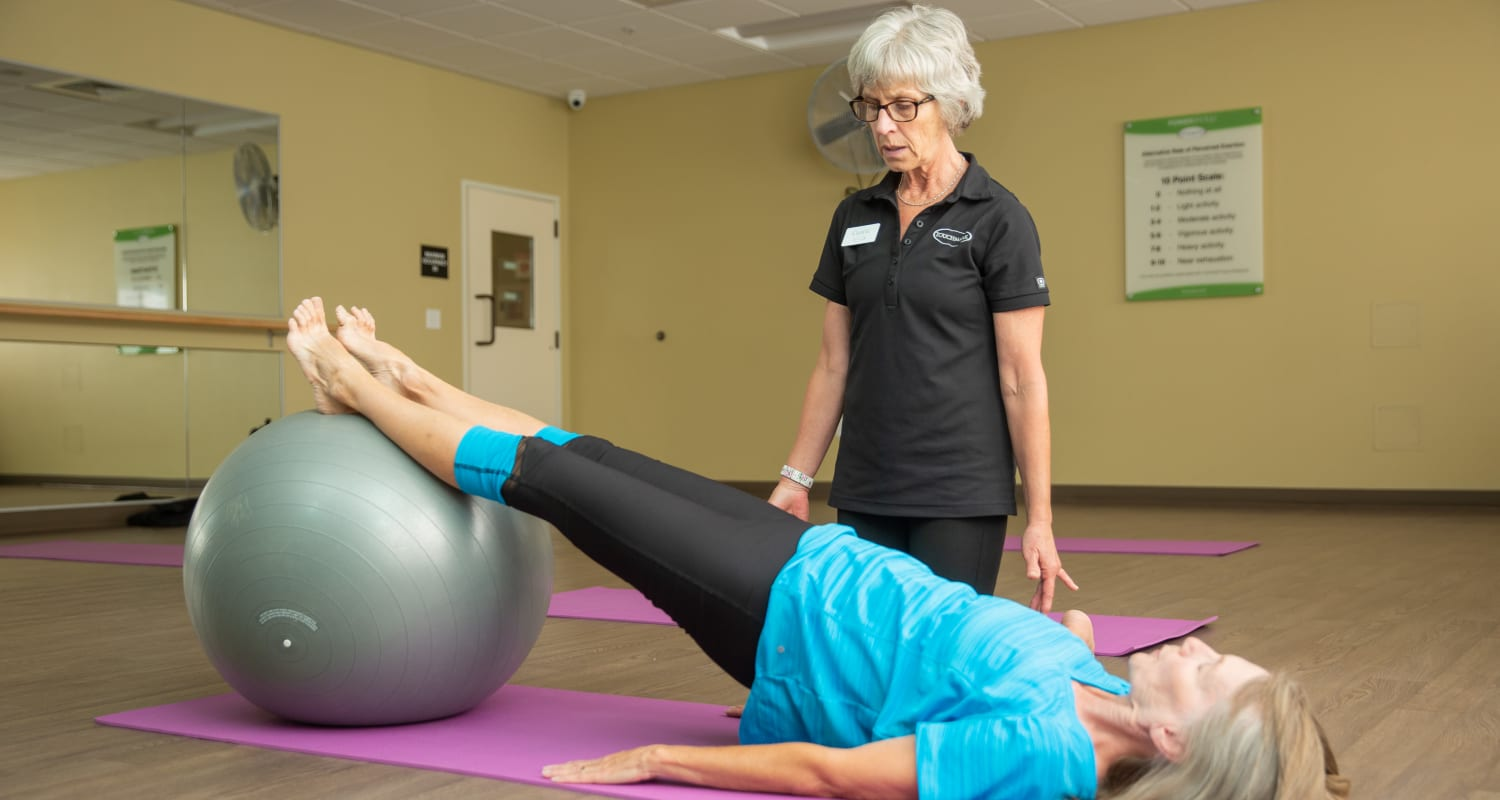 A caretaker assisting a fitness club member with an exercise at Touchmark on West Century Health & Fitness Club in Bismarck, North Dakota