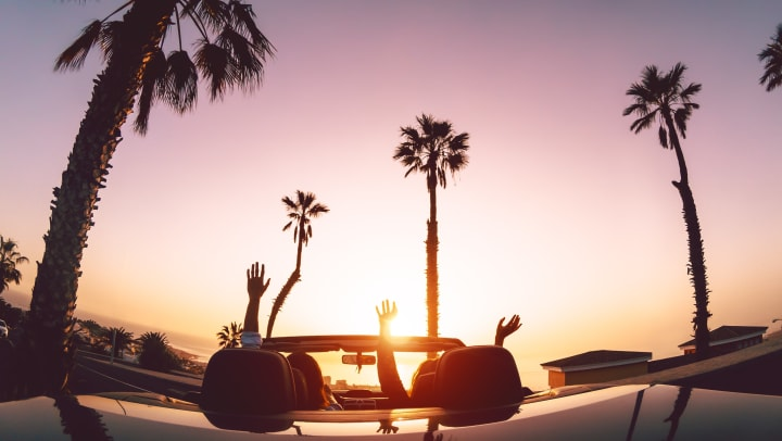 Image of two people in a convertible car driving with palm trees in the background