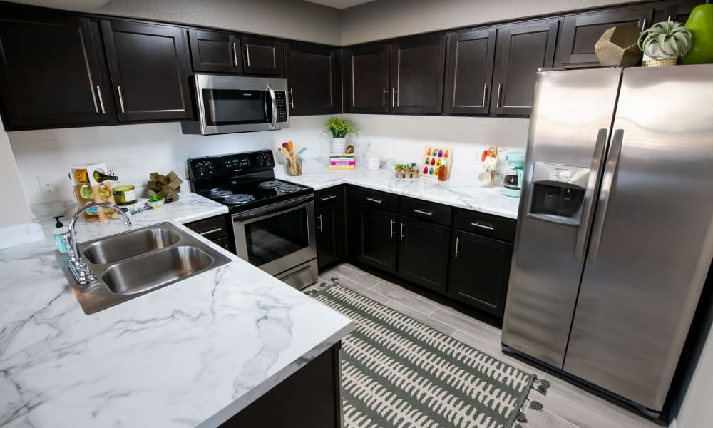 Espresso cabinets and white counter tops in kitchen at Portico at Friars Creek Apartments in Temple, Texas