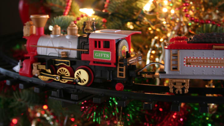 A model train on a track in front of a decorated holiday tree.